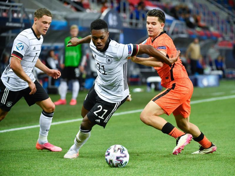 U21-Nationalspieler Ridle Baku (M.) setzt sich im EM-Halbfinale im Zweikampf gegen den Niederländer Ferdi Kadioglu (r) durch. Foto: Marton Monus/dpa
