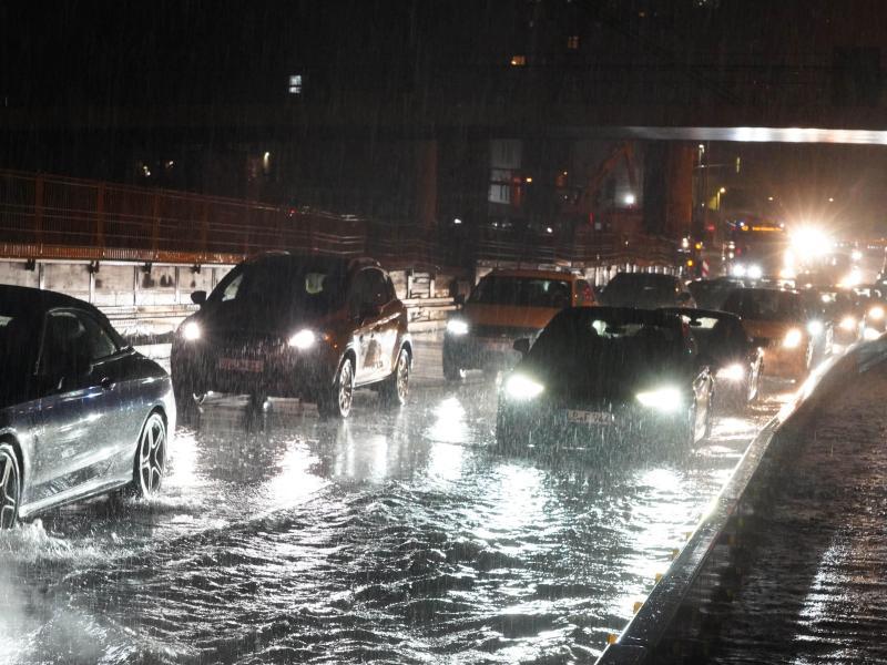 Autos fahren über die überflutete Schillerstrasse am Stuttgarter Hauptbahnhof. Foto: Andreas Rosar/dpa