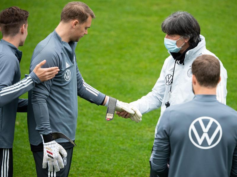 Manuel Neuer zeigt Bundestrainer Joachim Löw die Torwarthandschuhe für sein 100. Länderspiel. Foto: Federico Gambarini/dpa