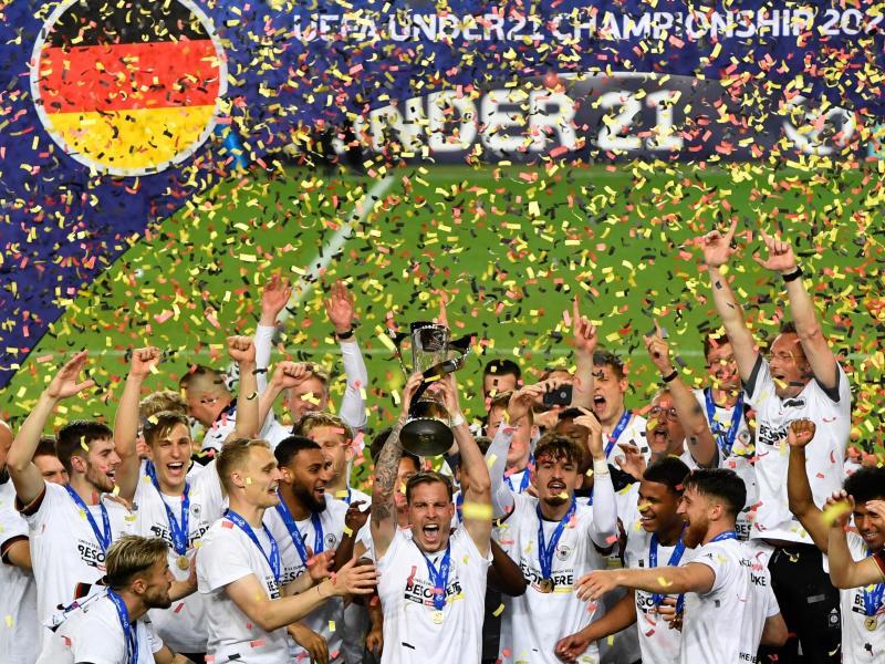 Die Spieler der deutschen U-21 feiern im Konfettiregen die Europameisterschaft. Foto: Marton Monus/dpa