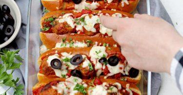 Bevor die Meatball Sandwiches im Ofen für 10 Minuten mit Mozzarella überbacken werden, kommen in jedes Briochebrötchen 3 Hackbällchen und etwas Soße. Foto: Mareike Pucka/biskuitwerkstatt.de/dpa-tmn