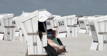 Touristen in einem Strandkorb am Strand von St. Peter-Ording. Foto: Bodo Marks/dpa