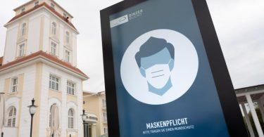 Ein Schild weist an einer Strandpromenade an der Ostsee auf die Maskenpflicht hin. Foto: Stefan Sauer/dpa
