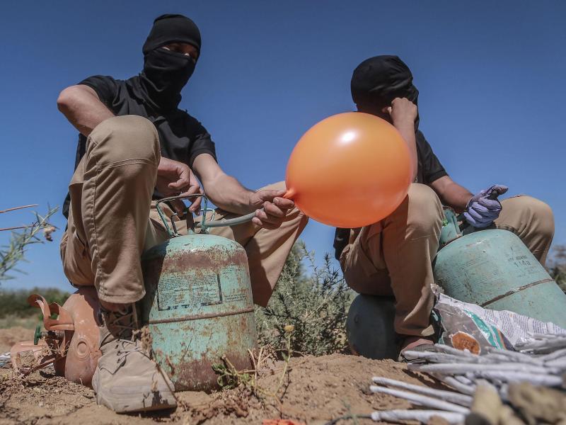 Maskierte Palästinenser präparieren Brandballons. Foto: Mohammed Talatene/dpa