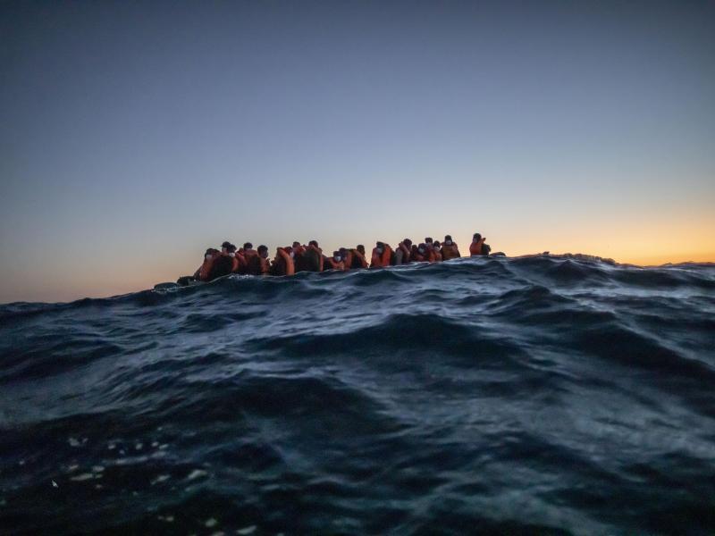Migranten aus verschiedenen afrikanischen Nationen warten in einem Boot vor der libyschen Küste im Mittelmeer auf Helfer. Foto: Bruno Thevenin/AP/dpa