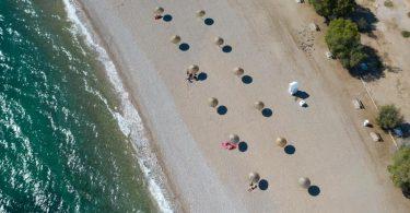 An einem Strand südlich von Athen stehen Sonnenschirme für Strandbesucher bereit. Wegen sinkender Corona-Infektionszahlen streicht die Bundesregierung am Sonntag Griechenland, fast ganz Frankreich, die Schweiz und Belgien von der Liste der Risikogebiete. Foto: Lefteris Partsalis/XinHua/dpa