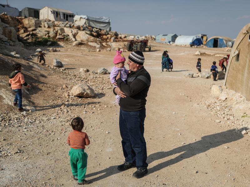 Ein Mann steht mit seinen Kindern in einem Flüchtlingslager in der Provinz Idlib. Foto: Anas Alkahrboutli/dpa/dpa