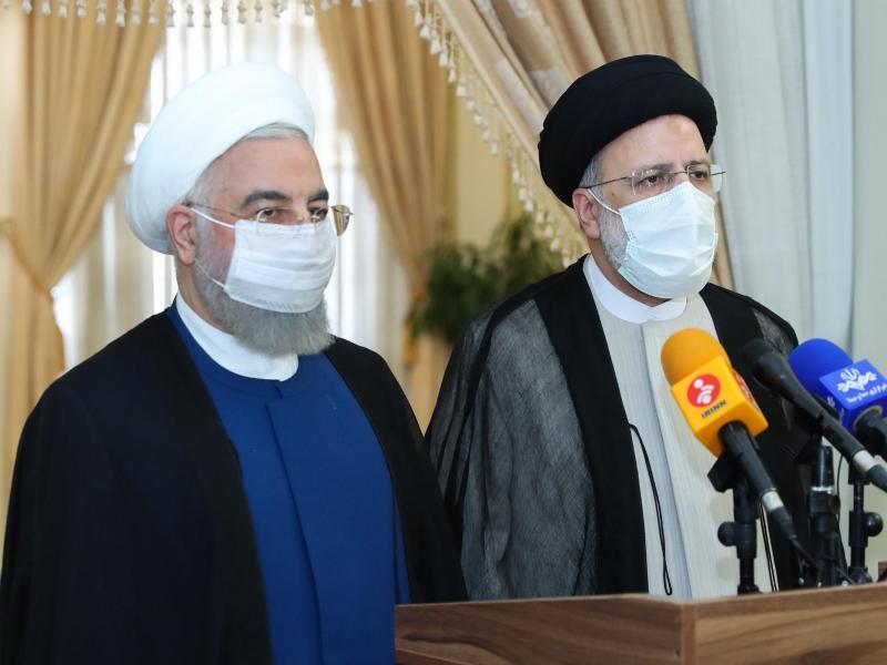 Der scheidende iranische Präsident Hassan Ruhani (l) tritt mit seinem gewählten Nachfolger Ebrahim Raeissi vor die Presse. Foto: -/Iranian Presidency/dpa