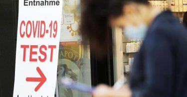 Eine Frau füllt vor einer Apotheke in Bonn ein Formular für einen Covid-19-Test aus. Foto: Oliver Berg/dpa
