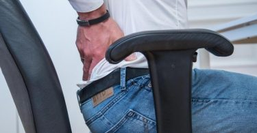 Problem und Lösung in einem Bild: Eine gekräftigte Muskulatur beugt Schmerzen vor - als Trainingshilfe im Büro können dabei auch die Armlehnen des Stuhls herhalten. Foto: Christin Klose/dpa-tmn