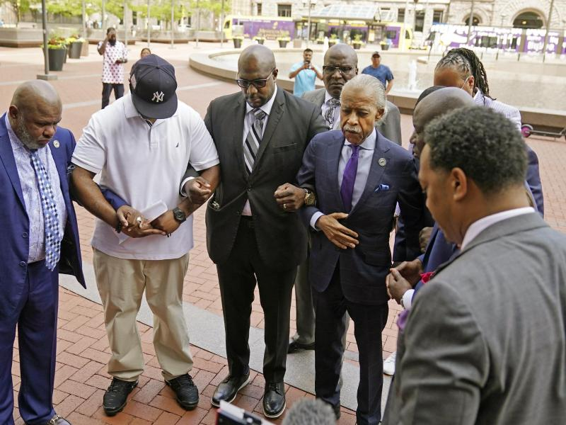 Bürgerrechtler Al Sharpton (M-r) zusammen mit Familienmitgliedern von George Floyd bei einem Gebet vor dem Betreten des Hennepin County Government Center. Foto: Jim Mone/AP/dpa