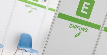 """Das Wort """"Impfung"""" ist an einem Aufsteller zu lesen im Impfzentrum Bielefeld. Foto: Friso Gentsch/dpa"""
