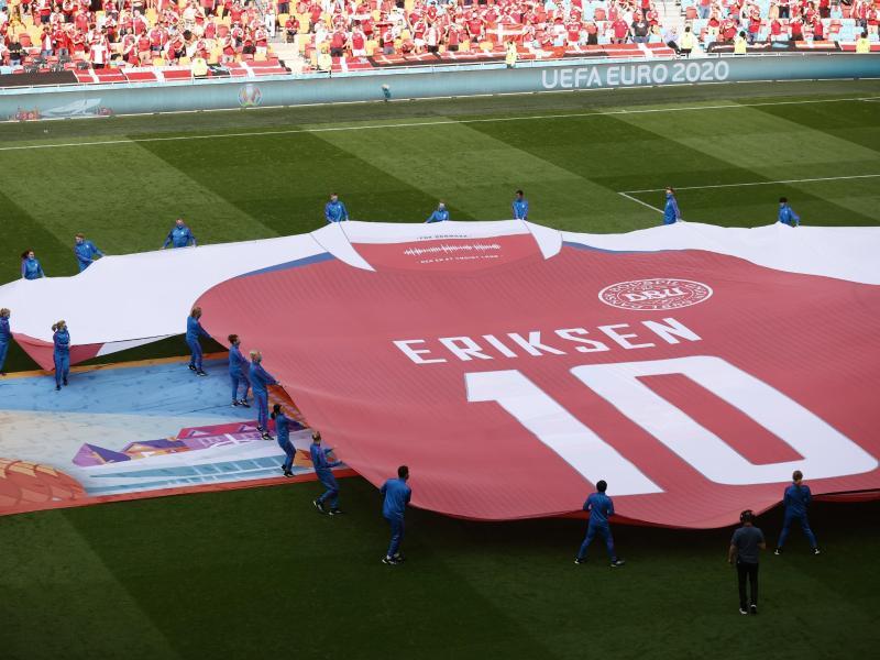 Ein riesiges Trikot des dänischen Spielers Eriksen wird vor dem Beginn des Spiels über das Feld getragen. Foto: Koen Van Weel/EPA Pool/dpa