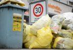 Mülltonnen und gelbe Säcke mit Kunststoff-Abfällen stapeln sich auf einem Fußweg. Foto: Sina Schuldt/dpa