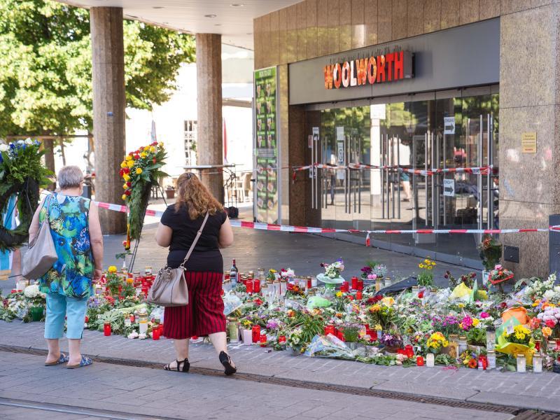 Trauerkerzen und Blumen liegen vor dem Kaufhaus, in dem der Täter Menschen mit einem Messer attackiert hatte. Foto: Nicolas Armer/dpa