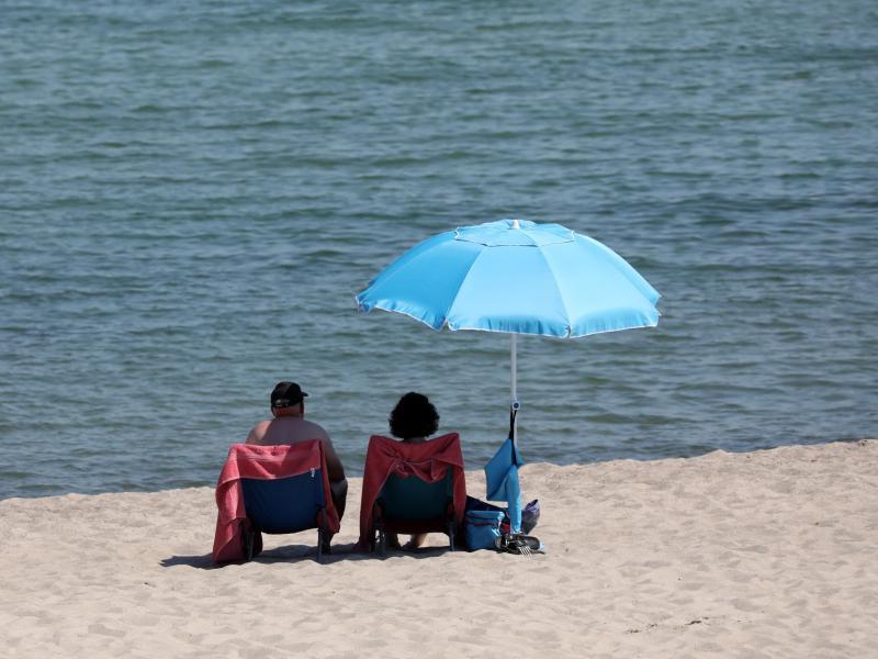 Urlauber genießen das warme Sommerwetter. Foto: Bernd Wüstneck/dpa