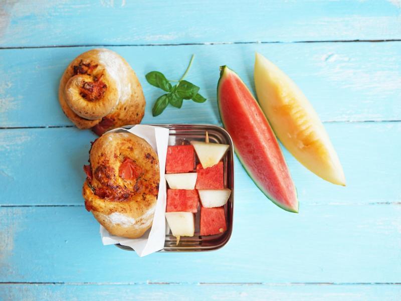 Mit Pizzaschnecken und Melonenspieße gibt es Herzhaftes und Süßes als Pausensnack. Foto: Manfred Zimmer/herrgruenkocht.de/dpa-tmn