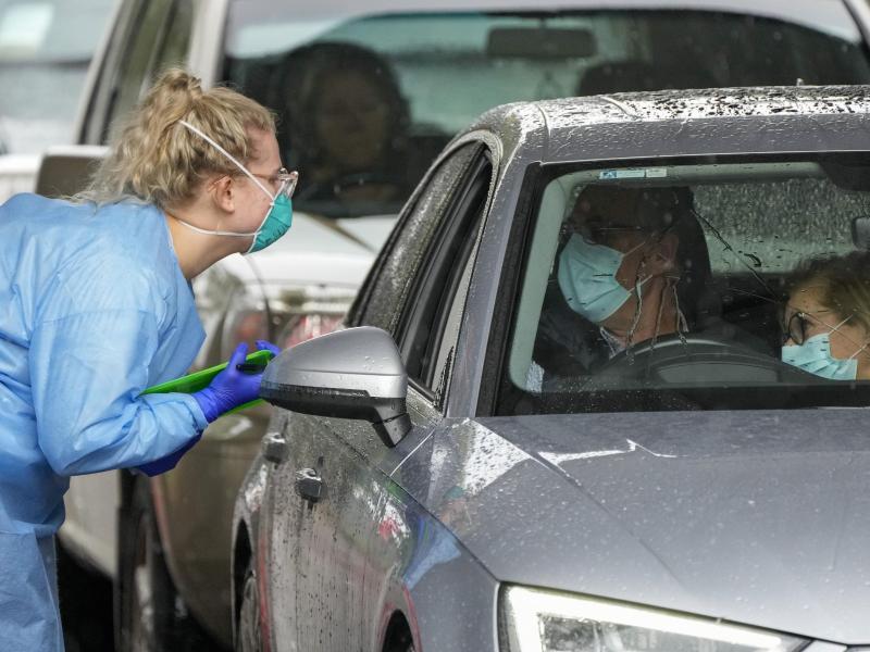 Eine Mitarbeiterin einer Teststation bereitet Autofahrer auf einen COVID-19-Test vor. Foto: Mark Baker/AP/dpa