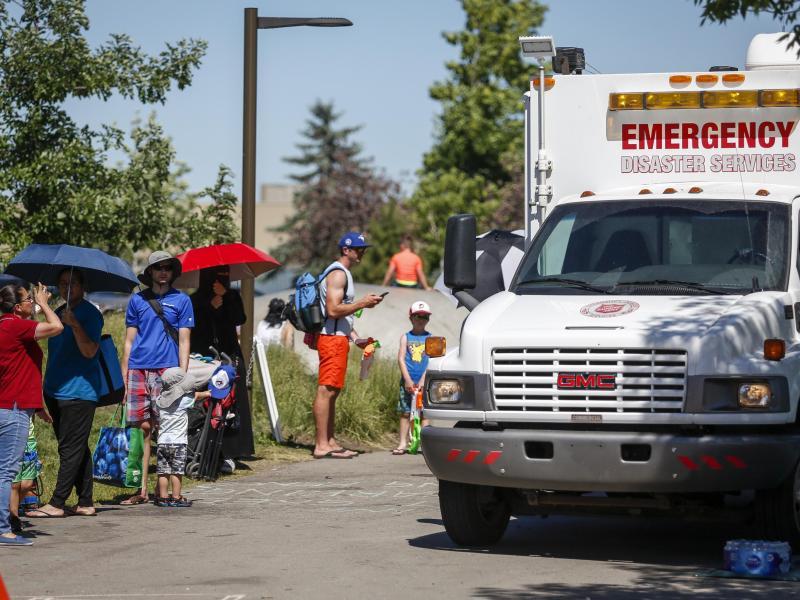 Ein Rettungswagen der Heilsarmee dient als Kühlstation, während die Menschen Schlange stehen, um in einen Wasserpark zu gelangen. Foto: Jeff Mcintosh/The Canadian Press via ZUMA/dpa
