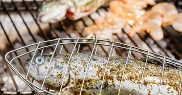Die Forelle brutzelt in der Fischzange. So kommt sie nicht mit dem Rost in Berührung. Und damit die Garnelen nicht in die Glut fallen, stecken sie auf einem Holzspieß. Foto: Monique Wüstenhagen/dpa-tmn