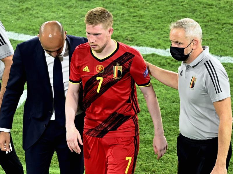 Belgiens Cheftrainer Roberto Martinez (l-r) und Physiotherapeut begleiten Kevin De Bruyne vomSpielfeld. Foto: Dirk Waem/BELGA/dpa