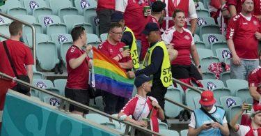 Ordner nehmen zwei Dänemark Fans eine Regenbogen-Fahne ab. Foto: Darko Vojinovic/Pool AP/dpa