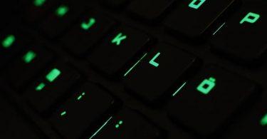 Ein Mann tippt auf einer beleuchteten Tastatur an einem Laptop. Foto: picture alliance / Nicolas Armer/dpa