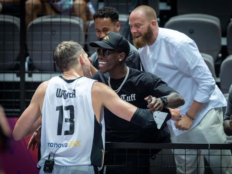 Zuschauer Dennis Schröder (M) beglückwünscht Moritz Wagner (l) nach der erfolgreichen Olympia-Qualifikation. Foto: Tilo Wiedensohler/dpa