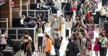 Reisende stehen am Flughafen am Security Check. Deutschland lockert die wegen der Verbreitung besonders ansteckender Corona-Varianten verhängten Einreisebeschränkungen unter anderem für Portugal und Großbritannien. Foto: Fabian Sommer/dpa