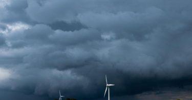 Eine Gewitterzelle mit dunklen Wolken zieht über Windräder in der Region Hannover hinweg. Foto: Julian Stratenschulte/dpa