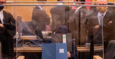 Der damals 27-Jährige Hauptangeklagte (vorne), seine Mutter (ganz hinten links) und ein dritter Angeklagter (roter Hefter) sitzen in einem Gerichtssaal des Landgerichts. Foto: Rolf Vennenbernd/dpa-Pool/dpa