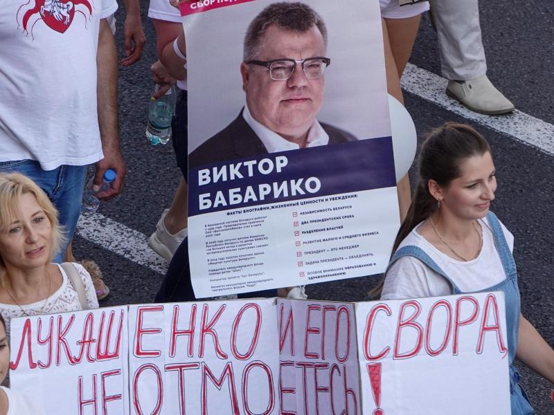 Menschen bei einer Demonstration gegen Machthaber Lukschenko mit einerm Transparent das den Oppositionellen Viktor Babariko zeigt. Foto: Ulf Mauder/dpa