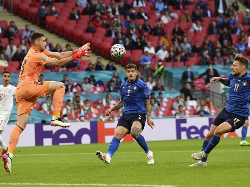Spaniens Torwart Unai Simon (l) fängt den Ball vor Italien-Torjäger Ciro Immobile (3.v.r). Foto: Andy Rain/Pool EPA/AP/dpa