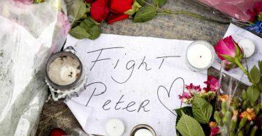 """Blumen, Kerzen und eine Botschaft mit """"Fight Peter"""" liegen am Tatort. Foto: Koen Van Weel/ANP/dpa"""