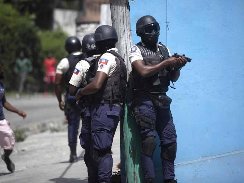 Polizisten mit gezogenen Waffen suchen nach Verdächtigen im Mordfall des haitianischen Präsidenten Jovenel Moise, in Port-au-Prince. Foto: Joseph Odelyn/AP/dpa