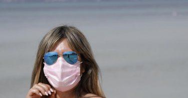 Maske am Strand: Auch 2021 steht der Sommerurlaub - wie hier auf Mallorca - ganz im Zeichen der Pandemie. Foto: Clara Margais/dpa