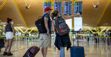 Reisende in einer Halle im Flughafen Madrid-Barajas. Foto: Manu Fernandez/AP/dpa