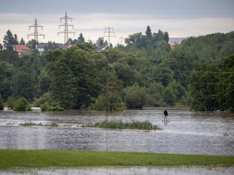 Das beste draus machen: Dieser Mann gleitet auf seinem Stand-Up-Paddle auf der über die Ufer getretene Zenn im bayrischen Lohe. Foto: Daniel Karmann/dpa