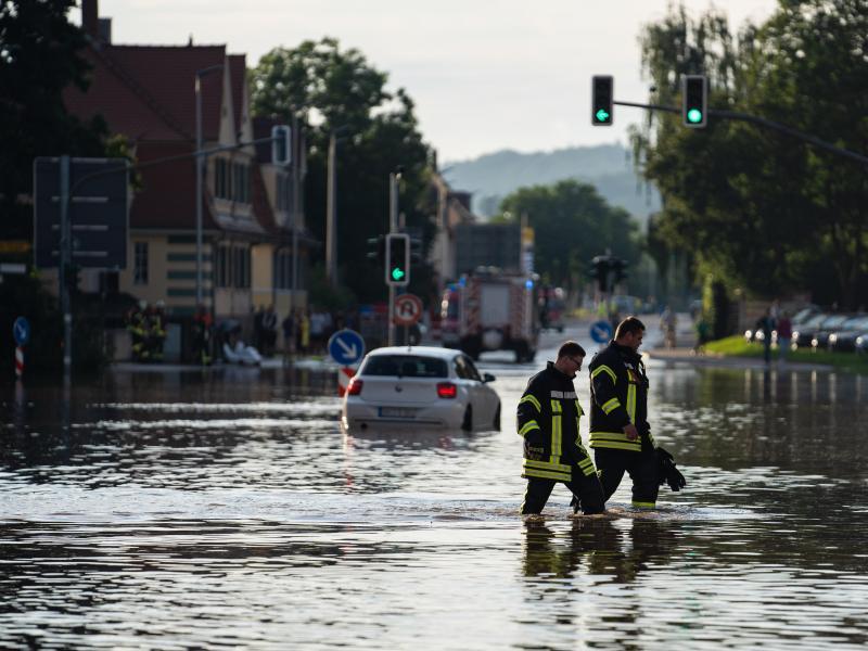 Einsatzkräfte der Feuerwehr waten über eine überschwemmte Kreuzung Ansbach. Foto: Nicolas Armer/dpa