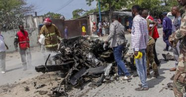 Sicherheitskräfte und Zivilisten stehen in der Nähe eines Autowracks nach dem ersten Anschlag im somalischen Mogadischu. Die islamistische Terrormiliz Al-Shabaab hat nun sechs weitere Mörsergeschosse abgefeuert. Foto: Farah Abdi Warsameh/AP/dpa