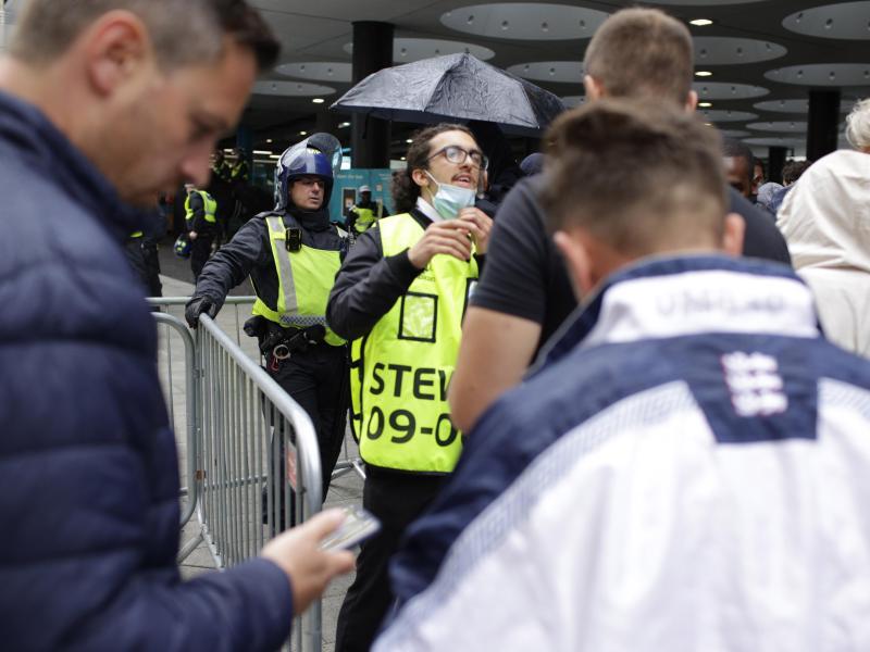 Stewards kontrollieren die elektronischen Tickets der Fans beim Betreten des Wembley-Stadions. Foto: David Cliff/AP/dpa