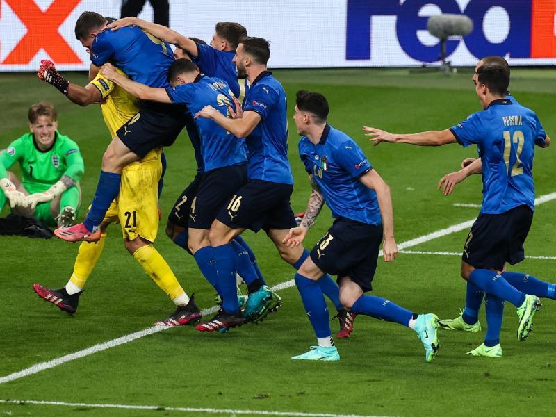 Italiens Spieler jubeln nach dem gewonnen Elfmeterschießen mit ihrem Torhüter Gianluigi Donnarumma. Hinten sitzt Englands Keeper Jordan Pickford. Foto: Christian Charisius/dpa