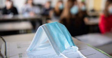 Eine Maske liegt auf einem Tisch in einer Münchner Schule. Foto: Matthias Balk/dpa