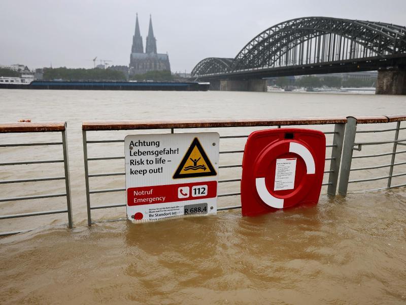 Land unter in NRW: Der Rhein überflutet die Promenade in Köln. Foto: Oliver Berg/dpa