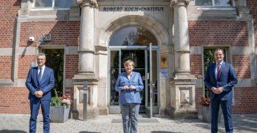 RKI-Präsident Lothar Wieler, Bundeskanzlerin Angela Merkel und Bundesgesundheitsminister Jens Spahn vor dem Eingang zum Robert Koch-Institut. Foto: Michael Kappeler/dpa-pool/dpa