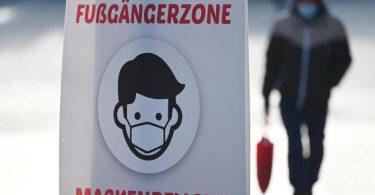 Ein Schild weist auf die Maskenpflicht in der Fußgängerzone hin. Foto: Marijan Murat/dpa