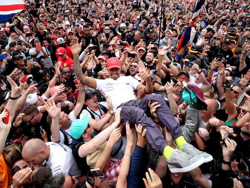 Bad in der heimischen Menge: Lewis Hamilton (M) feiert seinen Silverstone-Sieg 2019. Foto: David Davies/PA Wire/dpa