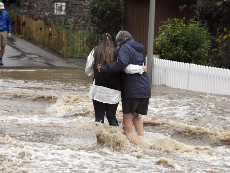 Anwohner der Ortschaft Balken helfen sich durch Fluten der Wupper. Foto: Roberto Pfeil/dpa
