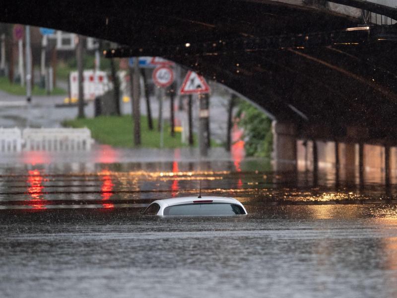 Nur das Dach eines Autos schaut noch aus dem Wasser, das eine Bahnunterführung geflutet hat. Foto: Marius Becker/dpa
