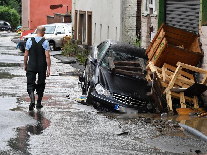 Durch heftigen Regenfälle war Flüsschen Nahma in Hagen zu einem reißenden Fluss geworden. Ein Anwohner schaut sich die verursachten Schäden an. Foto: Roberto Pfeil/dpa